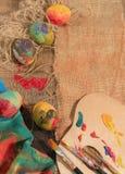 与两把画家的刷子、一个木调色板和一块手画布料的复活节五颜六色的鸡蛋 免版税库存照片