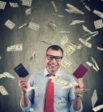与两本护照的愉快的商人在金钱雨下 免版税库存图片