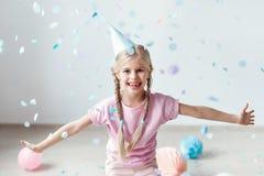 与两条猪尾的快乐的微笑的白肤金发的女性孩子,戴欢乐帽子,设法捉住在空气的飞行纸,获得乐趣 库存图片