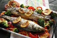 与两条鲜美鱼的烘烤盘和装饰 免版税库存照片