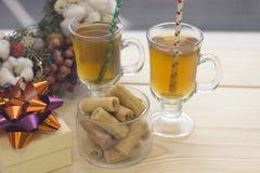 与两杯茶,碗曲奇饼和礼物盒的一个明亮的早晨 库存图片