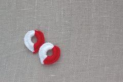与两棉花钩针编织红色和白色心脏的葡萄酒背景在亚麻布 圣诞节的手工制造被编织的装饰, Val 免版税库存照片