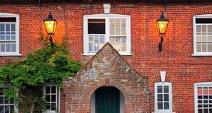 与两灼烧的灯笼的年迈的房子门面 免版税库存照片