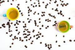 与两粒五颜六色的杯子和豆的咖啡样式 免版税库存图片
