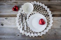 与两红色心脏的白色餐位餐具坐在木背景的白色鞋带小垫布 免版税库存照片