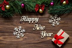 与两美丽的雪花和一个礼物盒的新年快乐在木背景的中心与杉树的 免版税库存图片