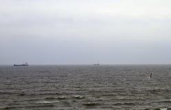 与两艘船、风筝冲浪者和波浪的灰色天空在海 图库摄影