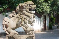与两头小狮子的狮子石雕象在后面在公园 图库摄影