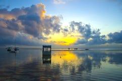 与严重的天空和小船的日出 免版税库存照片