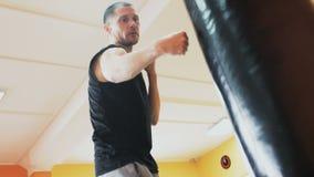 与个人教练的单独训练 教练员打在健身房锻炼的吊袋 肥胖人的减肥钻子 股票录像