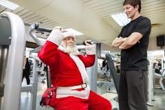 与个人教练员的圣诞老人在健身房 免版税库存照片
