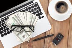 与个人计算机、咖啡杯、玻璃和金钱现金的办公室桌 库存照片
