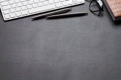 与个人计算机、笔记薄、玻璃、铅笔和笔的办公桌桌 免版税库存图片