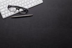 与个人计算机、玻璃和笔的办公室皮革书桌桌 免版税库存照片