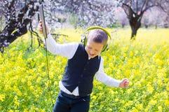 与个人计算机片剂和耳机的男孩跳舞 免版税库存照片