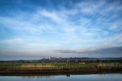 与中世纪城堡的惊人的充满活力的日出在安静反射了 免版税图库摄影