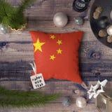 与中国旗子的新年快乐标记在枕头 在木桌上的圣诞装饰概念与可爱的对象 库存照片