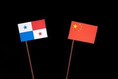 与中国旗子的巴拿马旗子在黑色 免版税库存图片