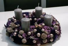 与中看不中用的物品和四个灰色蜡烛的紫色出现花圈在一张白色桌上 免版税图库摄影