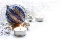 与中看不中用的物品和蜡烛的银色和蓝色圣诞节装饰 免版税库存图片