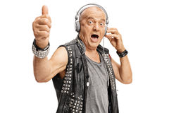 与举行他的赞许的耳机的年长punker 免版税库存图片