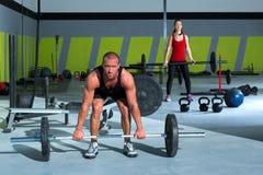 与举重棒锻炼男人和妇女的健身房 免版税库存图片