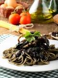 与乌贼墨水和新鲜的蕃茄的意大利面食 免版税库存照片