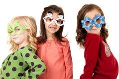 戴与乐趣expre的三个可爱的女孩滑稽的冬天眼镜 库存图片