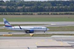 与乘出租车的小翅膀的太阳明确波音737-800航空公司装门在维也纳机场 免版税库存照片