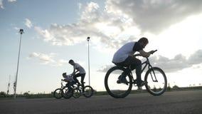 与乘坐在单车手和实践的自行车前轮离地平衡特技技术的凉快的少年的惊人的慢动作- 影视素材