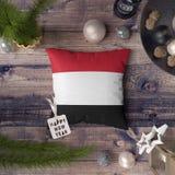 与也门旗子的新年快乐标记在枕头 在木桌上的圣诞装饰概念与可爱的对象 免版税图库摄影