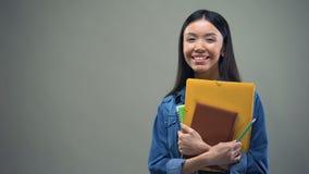 与习字簿在灰色背景,操作过程的亚洲妇女身分 股票视频