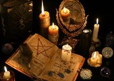 与书、灼烧的蜡烛和mirrow的不可思议的静物画 免版税库存照片