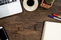 与书、笔、仙人掌和电话的布朗木办公桌桌 免版税库存照片