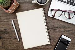与书、笔、仙人掌和电话的布朗木办公桌桌 库存照片