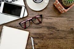与书、笔、仙人掌和电话的布朗木办公桌桌 库存图片