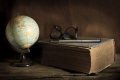 与书、笔和镜片的静物画地球 免版税库存图片