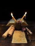 与书和纸卷的两个蜡烛 库存图片