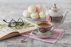 与书和茶的早晨用早餐在瓷茶杯 免版税库存照片