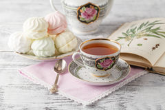 与书和茶的早晨用早餐在瓷茶杯 免版税库存图片