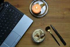 与书桌膝上型计算机和蜡烛的平的位置 免版税库存图片