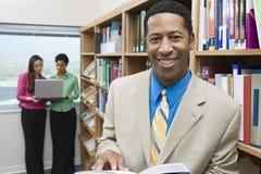 与书的商人在图书馆里 免版税图库摄影