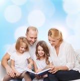 与书的愉快的家庭在家 库存照片
