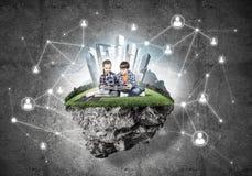 与书的探索这个伟大的世界的入学年龄两个孩子 免版税库存照片