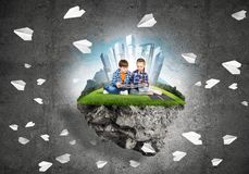与书的探索这个伟大的世界的入学年龄两个孩子 图库摄影