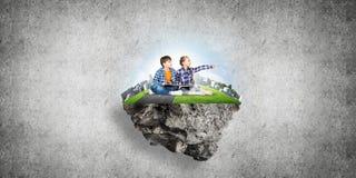 与书的探索这个伟大的世界的入学年龄两个孩子 库存照片