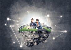 与书的探索这个伟大的世界的入学年龄两个孩子 免版税库存图片