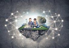 与书的探索这个伟大的世界的入学年龄两个孩子 库存图片