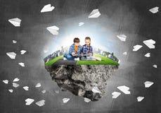 与书的探索这个伟大的世界的入学年龄两个孩子 免版税图库摄影