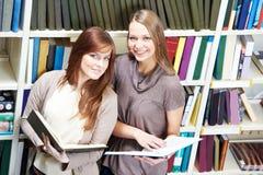 与书的新学员女孩研究在图书馆里 免版税库存图片